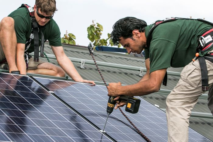 Two installers attach solar panels to a roof
